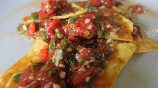 red hot salsa on corn chips by tiny chili pepper